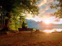 Man in green outdoor jacket  take photo, sit on wooden bench at lake. Royalty Free Stock Image
