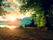 Man in green outdoor jacket  take photo, sit on wooden bench at lake. Royalty Free Stock Photography