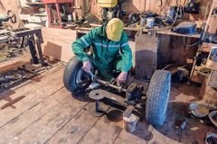 Man in green overall in workshop stock photos