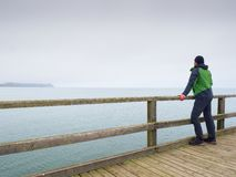 Man in green on sea mole at handrail. Autumn mist, rainy day. Man in green on sea mole at wooden handrail. Autumn mist, rainy day. Touristic on pier in harbor stock image