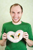 Man in green shirt holding big cracknel. With white topping and smiling Stock Images