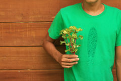Man in green shirt holding flowers Royalty Free Stock Image