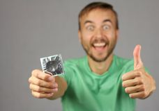 Man in green shirt holds a new condom in hand, make gesture thumb up, joy and anticipation of pleasure. Proper attitude to protection, gray background stock photo