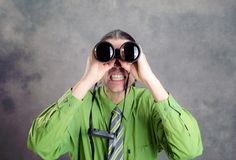 Man in green shirt and necktie looking through a binoculars. Young man in green shirt and necktie looking through a binoculars Royalty Free Stock Images
