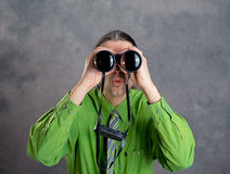 Man in green shirt and necktie looking through a binoculars. Young man in green shirt and necktie looking through a binoculars Royalty Free Stock Photography