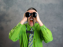 Man in green shirt and necktie looking through a binoculars. Young man in green shirt and necktie looking through a binoculars Stock Images