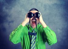 Man in green shirt and necktie looking through a binoculars Stock Photo