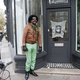 The man in green trousers and a leather jacket posing. Street fashion. LONDON, UK - APRIL 22, 2016: The man in green trousers and a leather jacket posing. Street royalty free stock image
