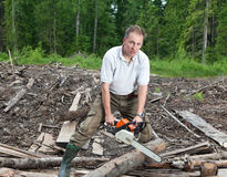 The man in green trousers and rubber boots works in the wood with a chain saw Stock Photography