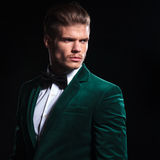 Man in a green velvet suit looking away. Side view of a serious young man in a green velvet suit looking away from the camera on black background Royalty Free Stock Photo