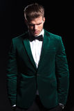 Man in a green velvet suit is looking down. Young man in a green velvet suit is looking down on black background Stock Images
