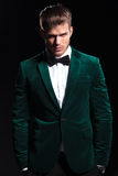 Man in green velvet suit is standing with hands in pockets Stock Image