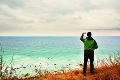 Man in green waterproof jacket takes photo of coastliny by smart phone. Cold windy day at sea. Stock Image