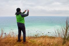 Man in green waterproof jacket takes photo of coastliny by smart phone. Cold windy day at sea. Royalty Free Stock Photos