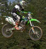 Man in Green White and Black Mtx Suit on Green and White 303 Dirt Motorcycle in the Air Royalty Free Stock Photos
