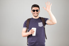 Man greeting someone. Man with coffee and backpack greeting someone isolated on gray background Royalty Free Stock Images