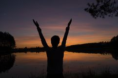 Man greeting sunset standing near the lake and.  Stock Photos