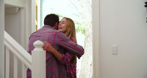 Man Greeting Visiting Girlfriend At Front Door. Man opens front door of house and greets visiting girlfriend with hug.Shot in 4k on Sony FS700 at frame rate of stock video footage