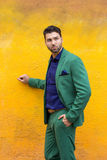 Man in gren suit on yellow wall background. Royalty Free Stock Image