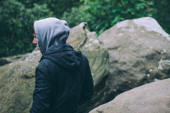 Man in Grey and Black Hooded Jacket Standing by Grey Rock Stock Photography