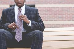 Man in Grey and Black Suit Jacket Sitting on Bench Royalty Free Stock Photo