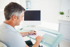 Man with grey hair highlighting information on a document. In his office Stock Photography