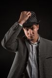 A man in a grey hat on black background Stock Photography
