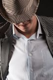 A man in a grey  hat on black background Stock Photo
