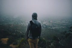 Man in Grey Hoodie Jacket Standing on Top of Mountain Royalty Free Stock Image