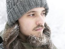A man in a grey knitted hat, with frosted beard and long hair in winter. Royalty Free Stock Photos