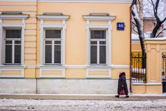 Man walk on snow street near yellow building in Moscow. A man in grey overcoat and wool hat with red bag in his left arm walking on snow street with yellow Royalty Free Stock Photos
