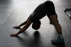 Man in Grey Shirt Doing Yoga on Gray Ceramic Tile Floor Royalty Free Stock Image