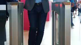 Man in grey suit jacket and blue jeans passing electronic turnstile with barcode scanner. Media. Access control for. Man in grey suit jacket and blue jeans stock video footage