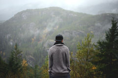 Man in Grey Sweater Standing Beside Mountain Royalty Free Stock Photography