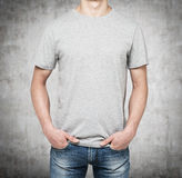 A man in a grey t-shirt and denims holds his hands in pockets. Stock Photo