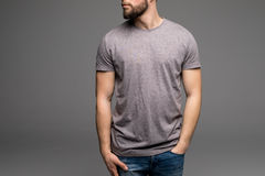 A man in a grey t-shirt and denims holds his hands in pockets. Stock Image