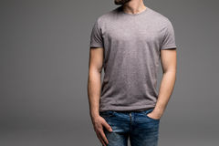 A man in a grey t-shirt and denims holds his hands in pockets. Stock Images