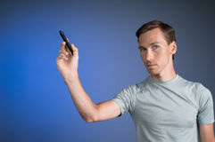 Man in grey t-shirt draws something on transparent screen, on blue background Royalty Free Stock Image