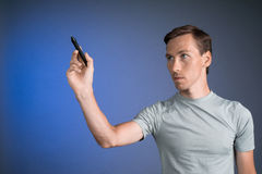 Man in grey t-shirt draws something on transparent screen, on blue background Stock Image