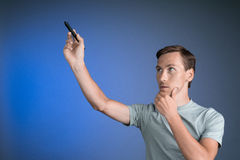 Man in grey t-shirt draws something on transparent screen, on blue background Royalty Free Stock Images