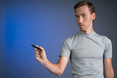 Man in grey t-shirt draws something on transparent screen, on blue background Stock Photo