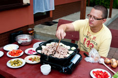 Man grilling. A man grilling outside his house, preparing Asian style food Stock Photos