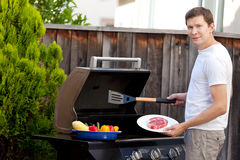 Man grilling food. Handsome young man ready for grilling meat and vegetables Stock Photo
