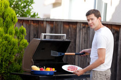 Man grilling food. Young handsome man ready for grilling meat and vegetables at his house backyard Royalty Free Stock Image