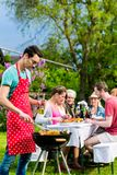 Man grilling meat on garden barbecue party Stock Images