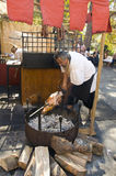 Man grilling a pice of meat on the medival market Stock Photos