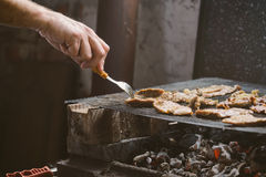 Man grilling pork meat chops on barbecue Royalty Free Stock Photography