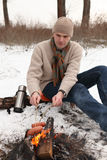 Man grilling sausages at campfire in winter Stock Image