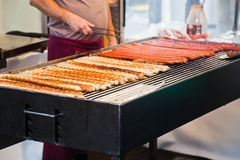 Man grills Frankfurter sausages Stock Photography