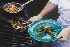 Man grills some kind of vegetable on gas grill during summer time. Chef at white glove puts grilled vegetables on the plate. man grills some kind of vegetable on Stock Image